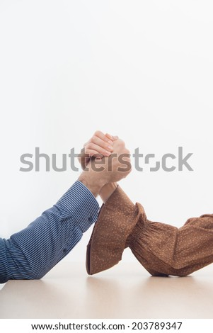 Closeup portrait of a young attractive woman and man fighting on hands isolated on white background - stock photo