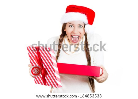 Closeup portrait of a young beautiful excited woman wearing red santa claus hat, opening gift box and super happy at what she gets, isolated on white background. Positive emotions, facial expressions - stock photo