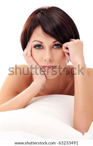 Closeup portrait of a young brunette woman lying in bed - stock photo