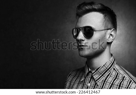 Closeup portrait of a young casual man looking away from the camera on gold background. Black and white concept. Fashion style - stock photo