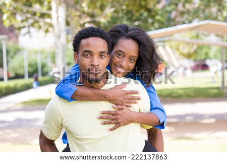 Closeup portrait of a young couple,guy giving woman piggy back ride, happy moments, positive human emotions on isolated outdoors outside park background.  - stock photo