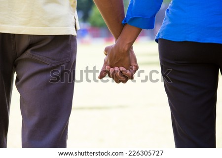 Closeup portrait of a young couple with chemistry, holding hands, happy moments, commitment, love and romance concept, positive human emotions on isolated outdoors outside park background. - stock photo