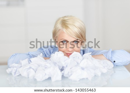 Closeup portrait of a young female executive with crumpled paper balls at desk - stock photo