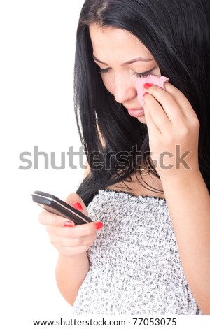 Closeup portrait of a young girl holding a mobile phone and crying - stock photo
