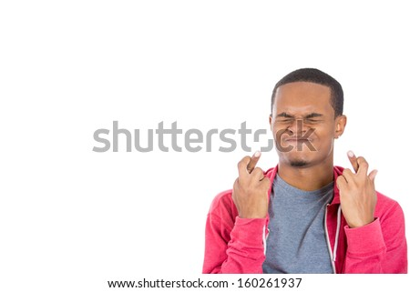 Closeup portrait of a young handsome man crossing fingers wishing and praying for miracle, hoping for the best, isolated on white background. Positive emotion facial expression feelings - stock photo