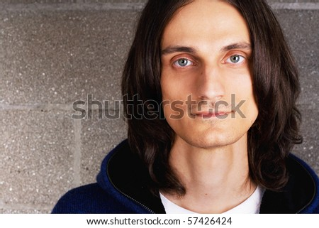 Closeup portrait of a young handsome man on a brick wall background - stock photo