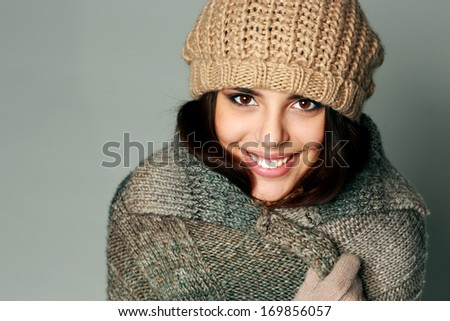 Closeup portrait of a young happy woman in warm winter outfit on gray background - stock photo