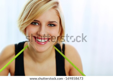 Closeup portrait of a young happy woman with measure tape - stock photo