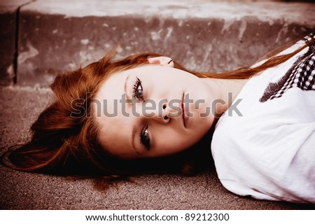 Closeup portrait of a young sad girl lying on asphalt - stock photo