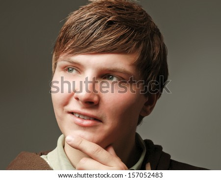 Closeup portrait of a young smiling guy, isolated on grey - stock photo