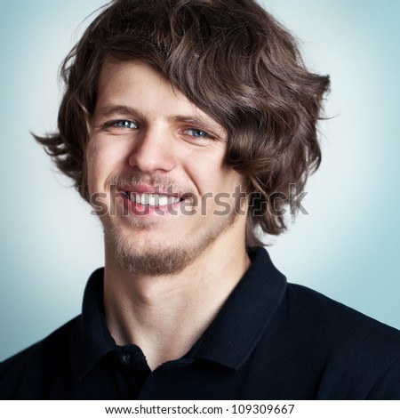 Closeup portrait of a young smiling man with curly hair . - stock photo