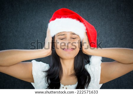 Closeup portrait of a young unhappy stressed helper woman with santa claus hat, covering ears and eyes to say stop making that loud noise it's giving me a headache, isolated on grey black background.  - stock photo