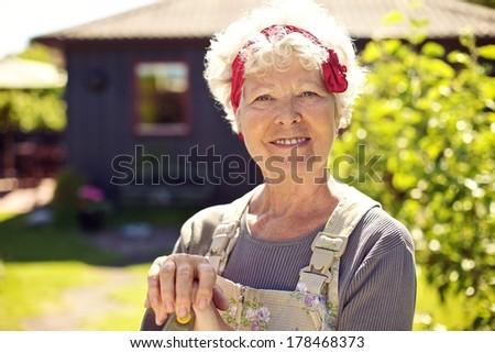 Closeup portrait of active senior woman standing in backyard garden - stock photo