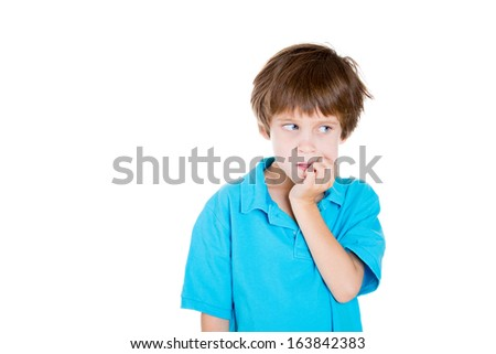 Closeup portrait of adorable boy in blue shirt looking sideways while biting fingernails because of craving for something or anxiety isolated on white background with copy space to left. Negative  - stock photo