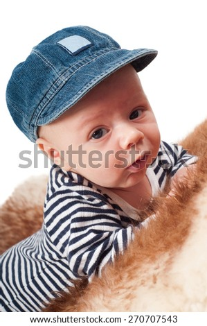 Closeup portrait of adorable child in denim hat lying on fur - stock photo
