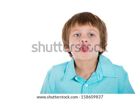 Closeup portrait of adorable kid sticking out tongue at camera gesture, isolated on white background with copy space - stock photo