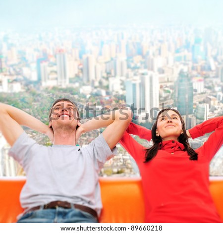 Closeup portrait of adult couple sitting on their sofa against big city panoramic view and dreaming about something. Planning future concept - stock photo