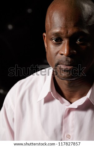 Closeup portrait of african man in pink shirt looking to camera - stock photo