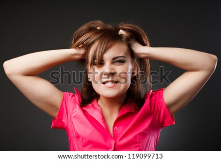 Closeup portrait of an angry woman pulling her hair - stock photo