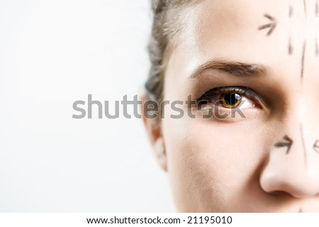 Closeup portrait of an attractive Caucasian woman whose face is marked with lines for facial cosmetic surgery - stock photo