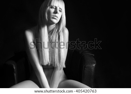 Closeup portrait of an attractive nude blond woman on black armchair, all nudity covered by her hair and hands, monochrome photo with copy space on the right side of the image - stock photo