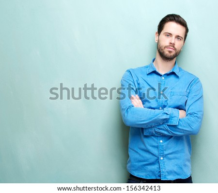 Closeup portrait of an attractive young man looking at camera with arms crossed - copy space - stock photo