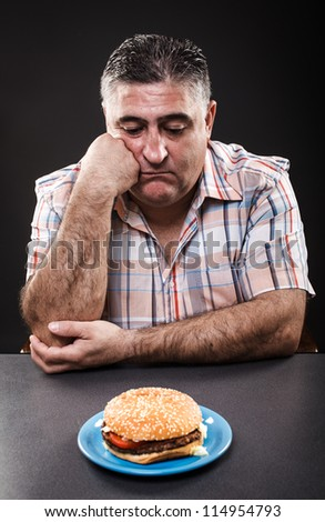Closeup portrait of an unhappy man looking at burger on gray background - stock photo