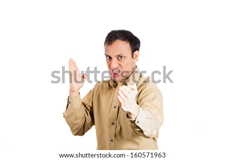 Closeup portrait of angry, mad, furious man, worker, employee, businessman in brown shirt raising hands in the air with karate chop, isolated on white background with copy space. Human emotions - stock photo