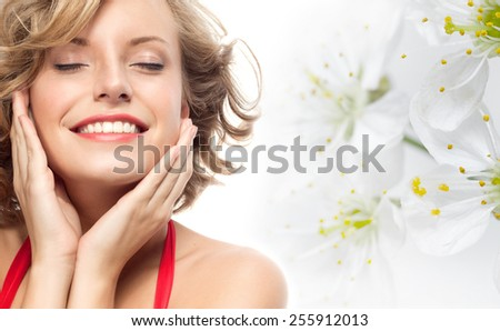 closeup portrait of attractive  caucasian smiling woman blond isolated on white studio shot lips toothy smile face hair head and shoulders looking at camera eyes closed spring flowers - stock photo