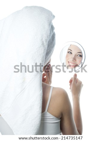 closeup portrait of attractive  caucasian smiling woman brunette isolated on white studio shot lips toothy smile face hair head and shoulders looking at mirror towel tube cleaning face cotton disc - stock photo