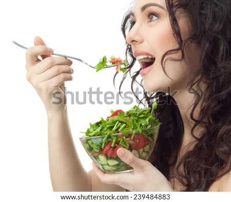 closeup portrait of attractive  caucasian smiling woman brunette isolated on white studio shot lips toothy smile face hair head and shoulders eating salad - stock photo
