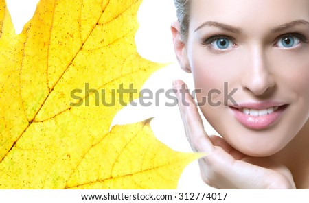 closeup portrait of attractive  caucasian smiling woman brunette isolated on white studio shot lips toothy smile face hair head and shoulders looking at camera tooth yellow maple leaf autumn - stock photo