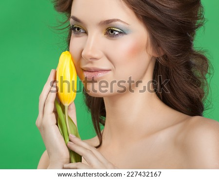 closeup portrait of attractive  caucasian smiling woman brunette studio shot lips  face hair head and shoulders skin makeup yellow flower aroma spring summer - stock photo
