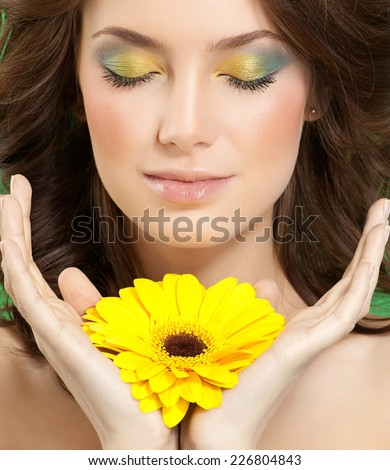 closeup portrait of attractive  caucasian woman brunette studio shot lips face hair head and shoulders skin makeup yellow flower eyes closed hands - stock photo