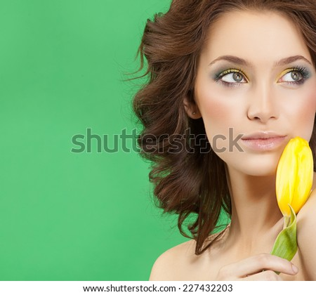 closeup portrait of attractive  caucasian  woman brunette  studio shot lips  face hair head and shoulders skin makeup yellow flower aroma spring summer - stock photo