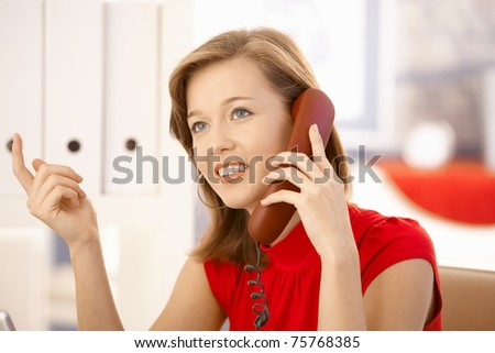 Closeup portrait of attractive office worker, talking on landline phone, gesturing. - stock photo