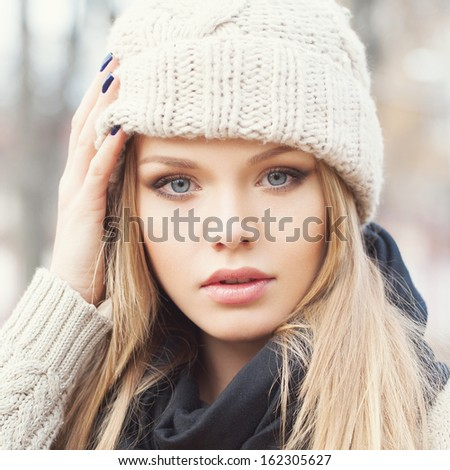 Closeup portrait of attractive young blonde girl with hand next to her cap. Looking at camera. Outdoors - stock photo