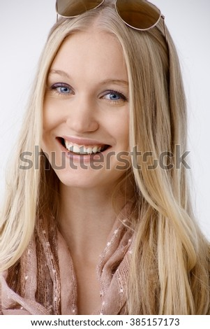 Closeup portrait of attractive young blonde woman with sunglasses on top of head, smiling, looking at camera. - stock photo