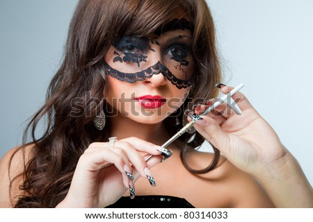 Closeup portrait of attractive young brunette girl with long dark ringlets and fine art manicure wearing lacy mask on her eyes holding graceful silver mouthpiece on blue background - stock photo