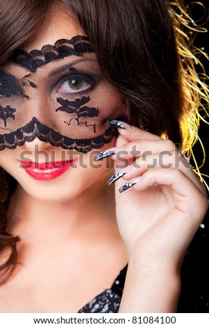 Closeup portrait of attractive young brunette girl with long dark ringlets fine art manicure wearing lacy mask on her eyes - stock photo