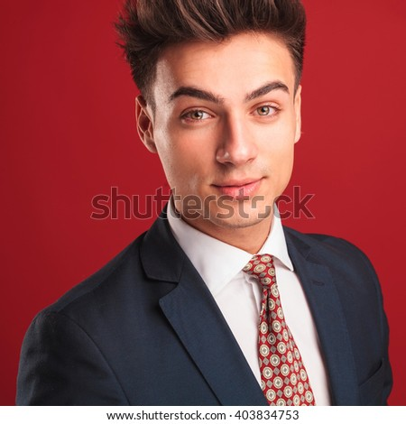 closeup portrait of attractive young businessman in black suit with red tie, posing in red studio background while looking at the camera - stock photo