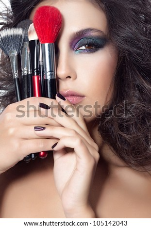 closeup portrait of attractive  young caucasian woman brunette isolated on white studio shot face skin makeup hands brushes hair looking at camera eyes - stock photo