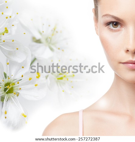 closeup portrait of attractive young caucasian woman brunette isolated on white studio shot lips face hair head and shoulders looking at camera spring flowers - stock photo