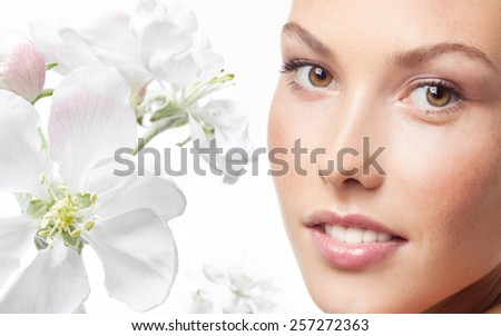 closeup portrait of attractive young caucasian woman  isolated on white studio shot lips face head and shoulders looking at camera tooth spring flowers - stock photo