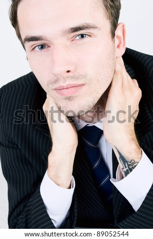 Closeup portrait of attractive young handsome man face, male model as businessman with hands on his neck - made in studio on white background - stock photo