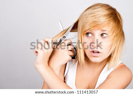 closeup portrait of attractive young woman with scissors - stock photo