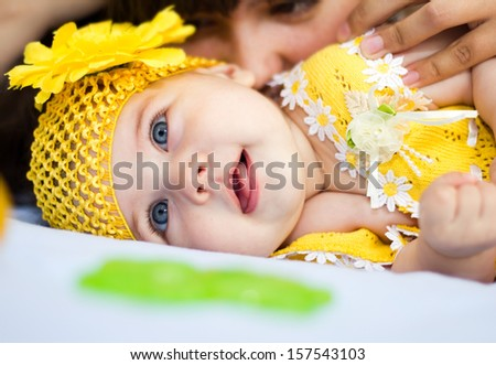 Closeup portrait of  baby girl in yellow with her mother - stock photo