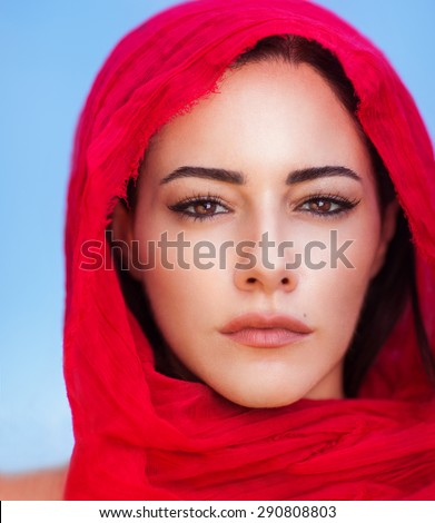 Closeup portrait of beautiful arabic woman wearing red headscarf over blue sky background, perfect natural makeup, traditional arabian beauty