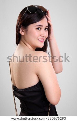 Closeup portrait of beautiful Asian girl in summer dress looking back and smiles - stock photo