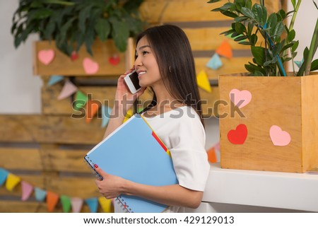 Closeup portrait of beautiful Asian student communicating over mobile or smart phone while waiting for her classmates in library, college or university. - stock photo